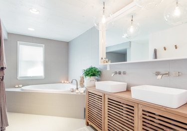 Modern double vanity with white trough sinks, large mirror, corner bathtub and Wall-Mounted Bathroom Faucet