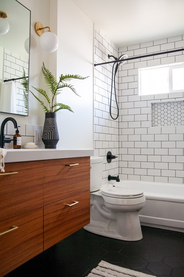 small midcentury modern bathroom with black and white vase and shower with white subway tile