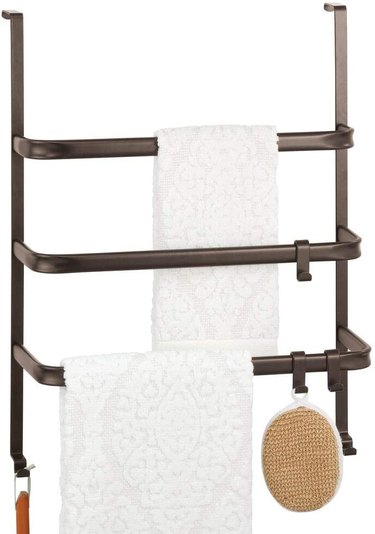 Door towel rack for small bathroom with three bars and white towels