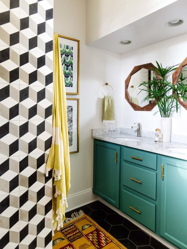 small midcentury modern bathroom with green cabinets and black and white tiled wall