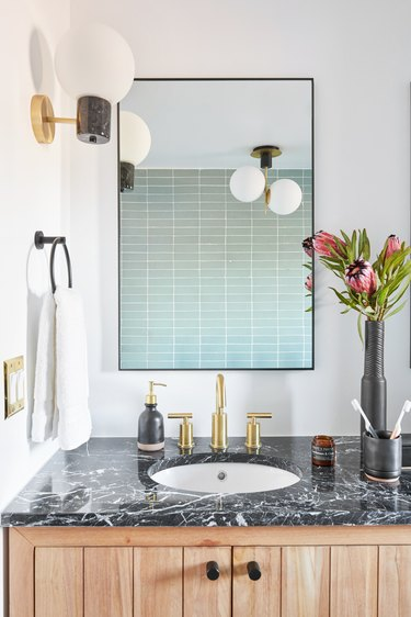 small midcentury modern bathroom with blue tile wall and globe-style light fixtures