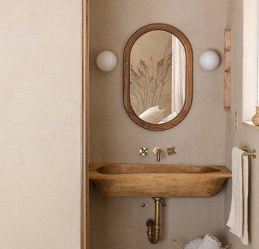 Wood sink, brass Wall-Mounted Bathroom Faucet, oval mirror, vanity lights.