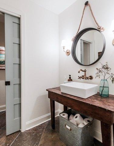 Light blue small bathroom door with white farmhouse bathroom