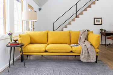 yellow couch near stairs with gray rug and side table