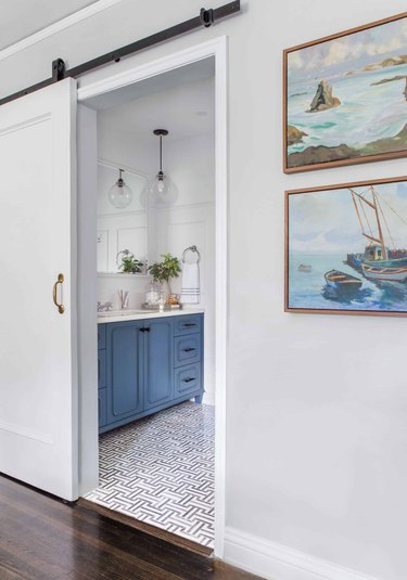 White sliding small bathroom door with blue vanity cabinet and patterned floor tile