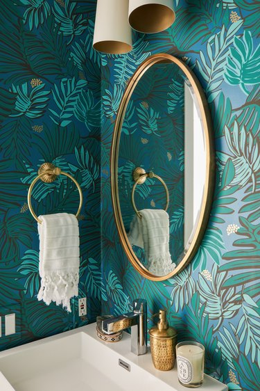 small boho bathroom with green floral wallpaper and brass fixtures