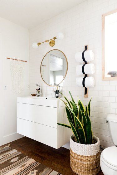 Boho Bathroom Storage in modern boho bathroom with brass details and towel holder