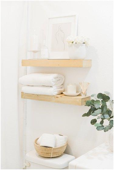 Boho Bathroom Storage in boho wooden open shelving above toilet