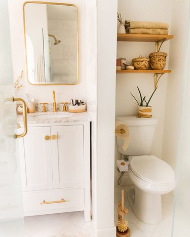 small boho bathroom with brass hardware and open shelving