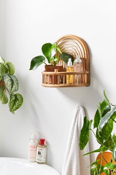 small boho bathroom with rattan wall shelf with plants next to a tub
