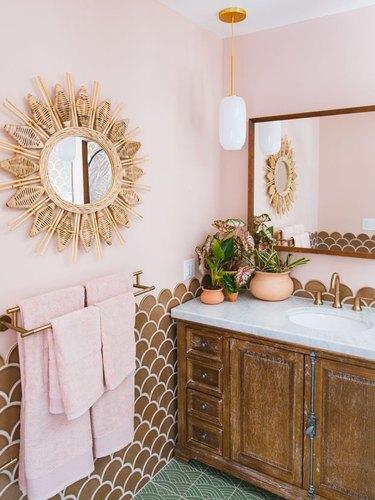 small boho bathroom with pink wall and brown backsplash and sunburst mirror