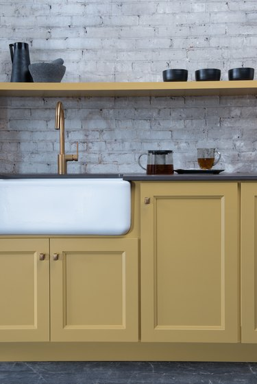 kitchen with yellow cabinets and shelves