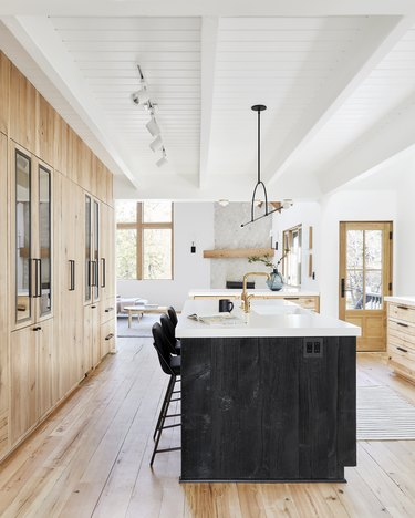 Rustic modern kitchen with black island and modern light fixture
