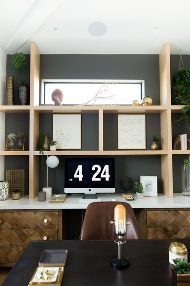 dark gray home office with wood shelves and bohemian decor