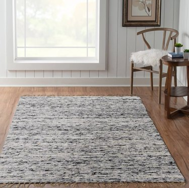 gray and white reversible area rug on wood floor