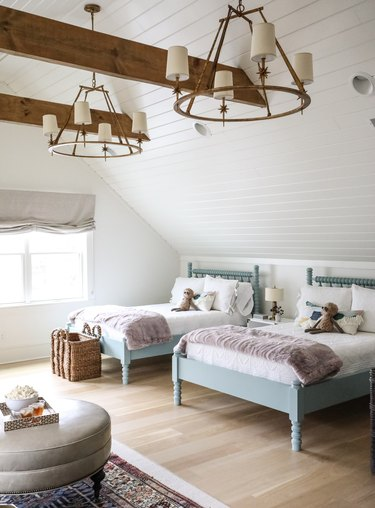 large farmhouse chandeliers on paneled ceiling above twin beds