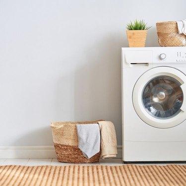 white washing machine next to wicker basket of laundry