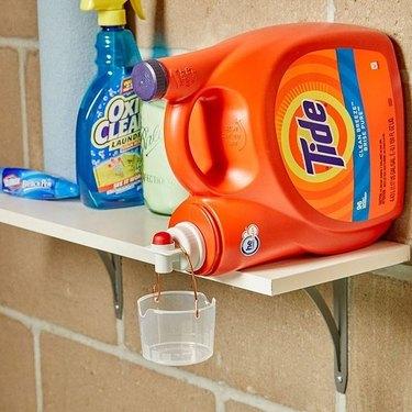 tide detergent bottle on shelf with plastic detergent cup hanging off it