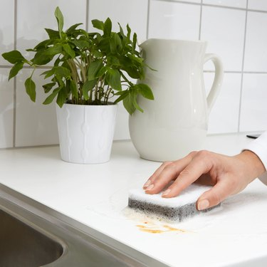 person cleaning countertop with sponge