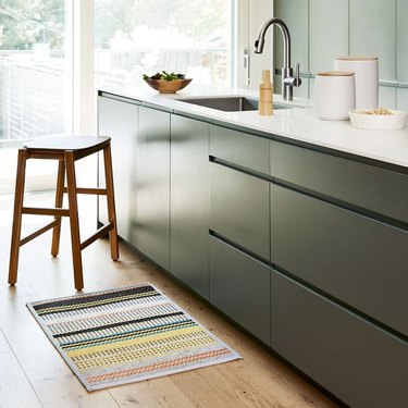 kitchen with green cabinets and colorful mat beneath the sink