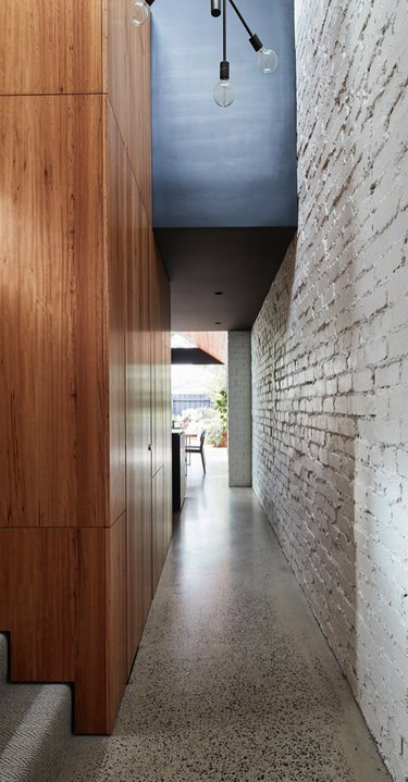 Modern Hallway with wood paneling, brick wall, terrazzo floors.