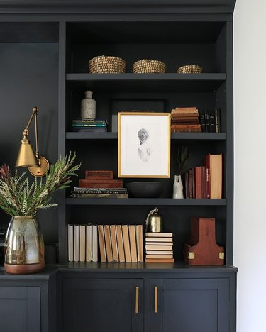 matte black bookcase with books, baskets, art, and vases