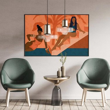 sitting area with painting of two women on orange stairwell and light green armchairs