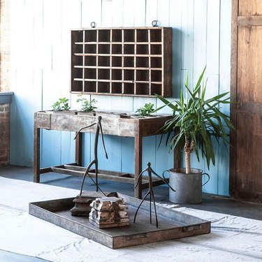 wood wall cubby above wood table and plant in metal pot