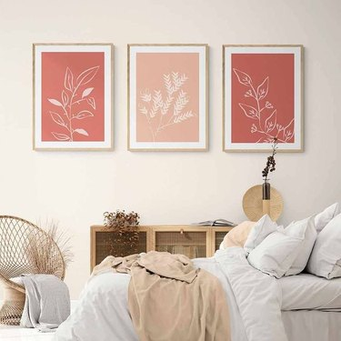 three pink plant art prints on wall above bed with white linens