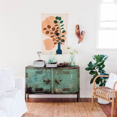 plant art tapestry and wooden shoe wall art above rusted green cabinet