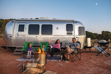 family sitting in front of airstream