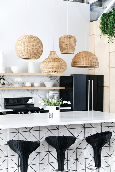 woven wicker pendant lights in various shapes above black and white modern island