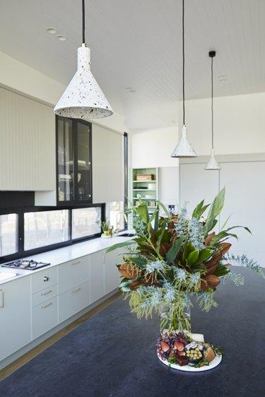 white terrazzo pendant lights above black island with fresh flowers
