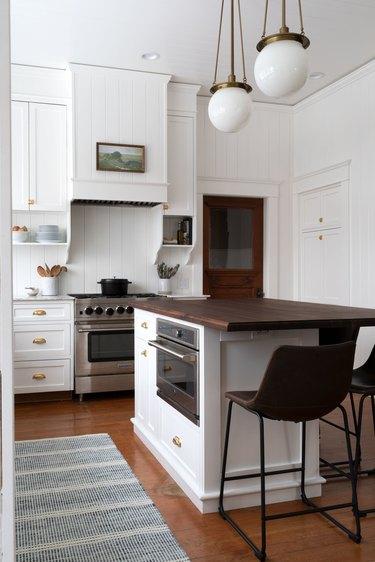wood kitchen island with white milk glass globe style lights
