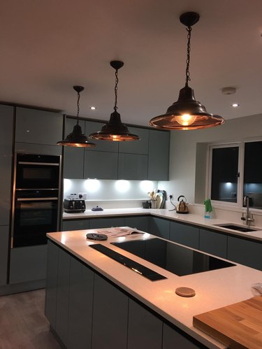 black and copper pendant lights above island in dimly lit kitchen