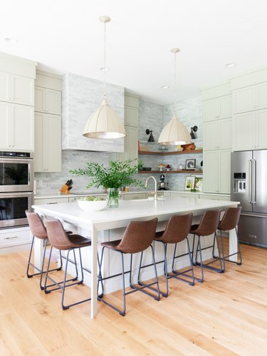 cream bell style pendant lights hanging above island with seating