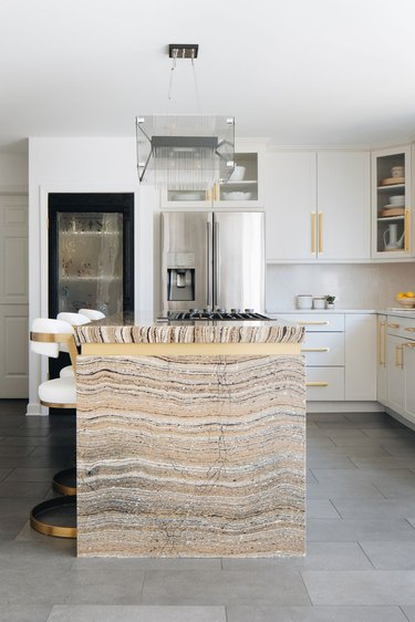 modern glass chandelier above brass and marble island