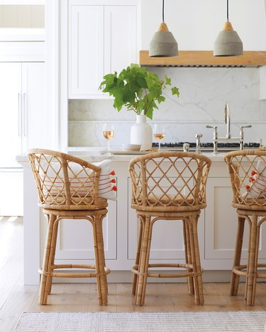 concrete pendant lights in white kitchen with rattan bar stools