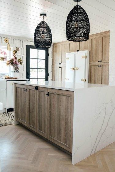black rattan lights above marble island in wood kitchen
