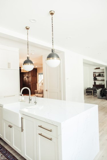 white and brass globe style pendant lights above white island