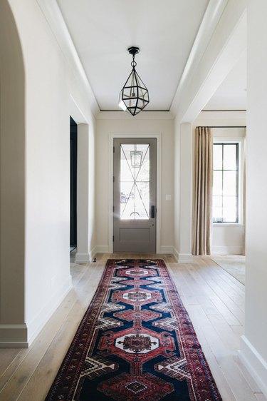 Entryway with glass pendant lamp, Oriental runner rug, wood floors.
