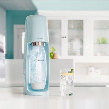 light blue sparkling water maker on white kitchen counter