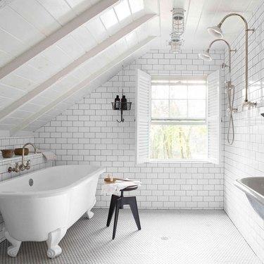 white attic bathroom with clawfoot tub and subway tile backsplash