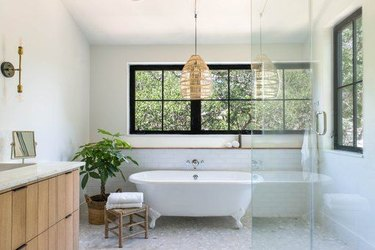white modern bathroom with freestanding clawfoot tub in front of a wall with windows