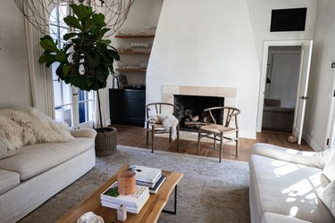 ivory colored living room with fireplace and fiddle leaf fig tree