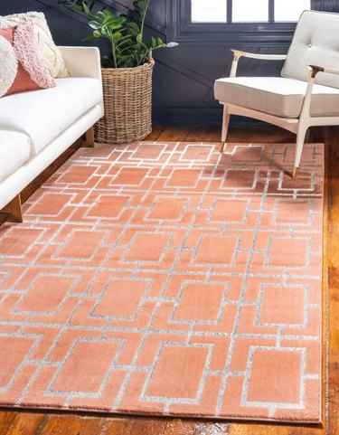 silver and orange geometric area rug in midcentury living space