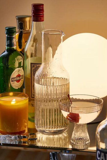 ridged glass pitcher next to glass and bar accessories, candle, and lamp