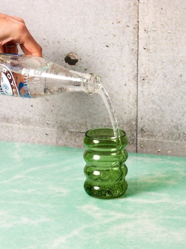 person pouring from glass bottle into green ripple glass