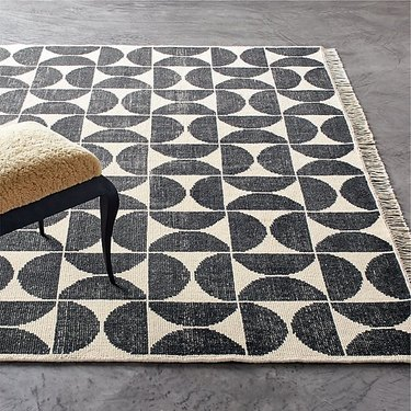 black and white geometric area rug with fringe on gray floor