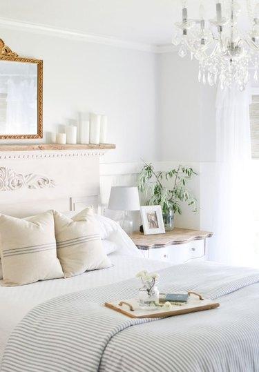 Farmhouse Chic Bedroom Ideas in Bedroom with chandelier, mirror, vintage headboard.